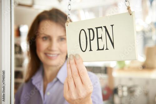 Fotografía  Store Owner Turning Open Sign In Shop Doorway