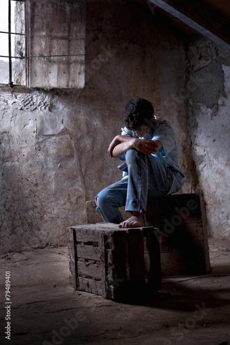 Fotografija  Young man, 12 years, dirty, mistreaded, sat in a garret