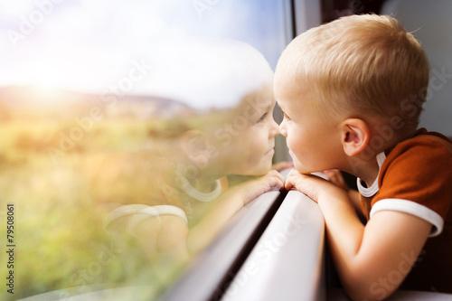 Plakat Mały chłopiec podróżuje w pociągu