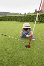 Young Girl Sitting By A Golf Course Hole.