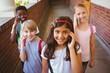 School kids using cellphones in school corridor