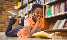 Cute African American Boy Reading Book In Library
