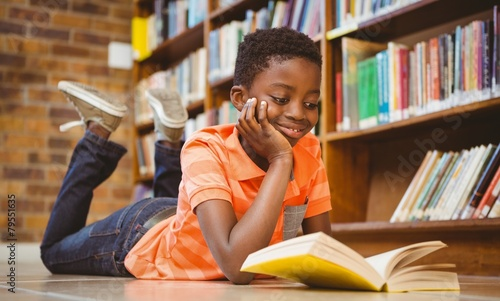 Cute african american boy reading book in library Canvas-taulu