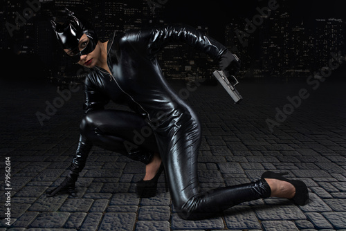 Fotografie, Obraz  Sexy female in black catwoman costume with gun
