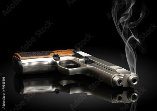 Photographie  Arme de poing sur fond noir avec de la fumée
