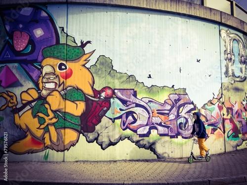 chlopiec-jedzie-hulajnoga-przy-graffiti-sciana