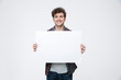canvas print picture - Happy man with curly hair holding blank billboard