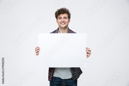Fotografering  Happy man with curly hair holding blank billboard