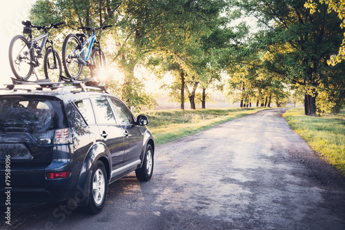 Fototapeta Car with bicycles in the forest road obraz