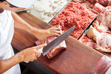 Smiling Butcher Cutting Meat A...