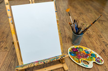 Easel Palette And Brushes With Empty White Canvas