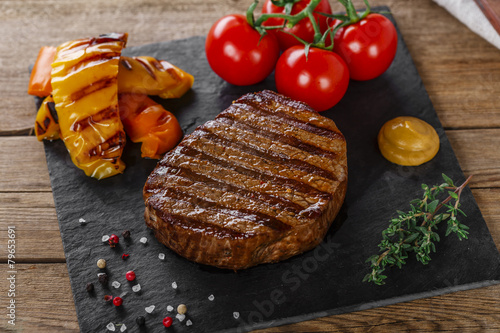 grilled beef steak with vegetables on a wooden surface Poster