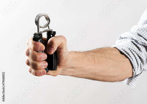 Fototapeta Male Hand Exercising Strength Using Hand Gripper