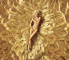 Blond Woman Lying On The Golden Wings