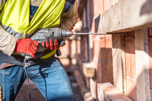 Worker using a drilling power tool on construction site