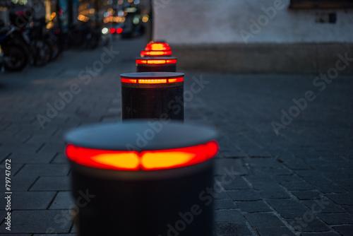 Fotografía  Absperrpoller beleuchtet bei Nacht