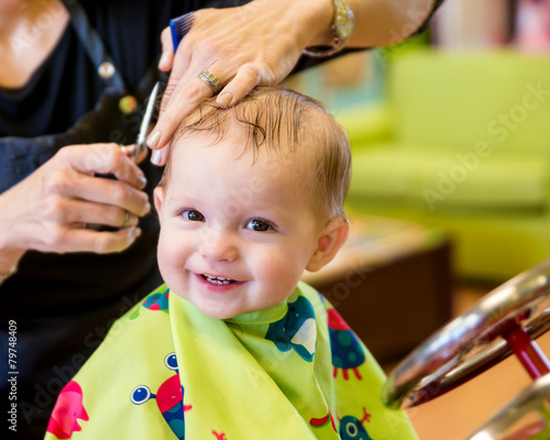 Photo  Happy toddler child getting his first haircut