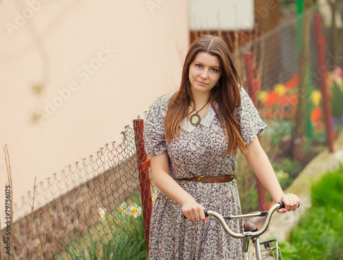 Fotografia, Obraz  Beautiful young woman in dress walk with old vintage bicycle