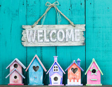 Welcome Sign Hanging Over Colorful Birdhouses
