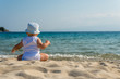 caucasian baby boy with a hat sitting on sand