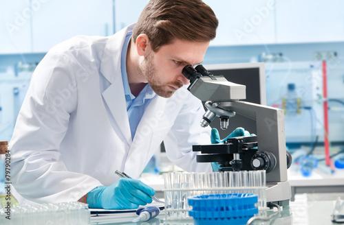 Fotografia  Scientist looking through a microscope in a laboratory