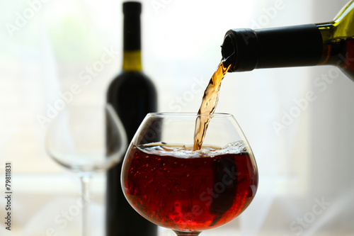 Poster de jardin Bar Red wine pouring into wine glass, close-up