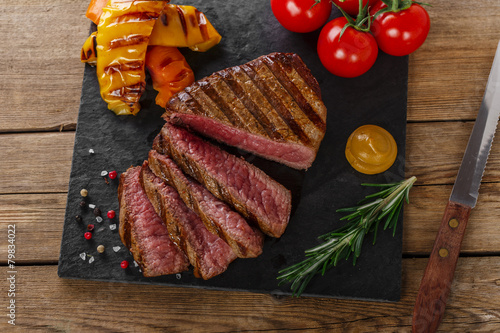Foto  grilled beef steak rare sliced with vegetables
