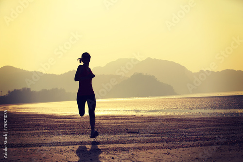 young healthy lifestyle woman running at sunrise beach adobe stock