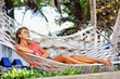 Woman is resting in the hammock under the palms on the tropical