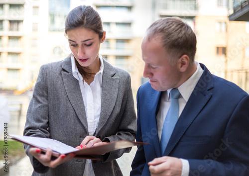 Foto  Zwei Geschäftsleute, die außerhalb des Büros sich besprechen