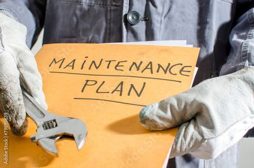 Worker holding a folder of maintenance plan and monkey wrench