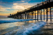 The pier and waves in the Pacific Ocean at sunset, in Oceanside,