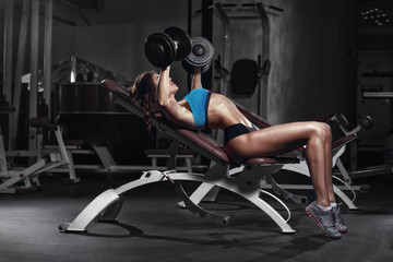 Fototapeta na wymiar fitness girl training chest with barbell at gym