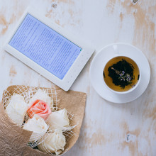 Tea, Roses And E-book On A Wooden Vintage Background