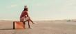 Leinwandbild Motiv Traveler girl sitting on a suitcase on road