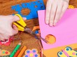Female that cut paper shapes for children