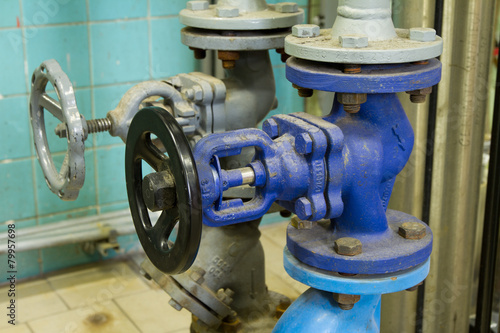 Photo  Pipes and faucet valves of heating system in a boiler room