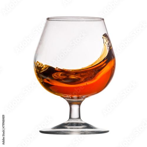 Foto op Canvas Alcohol Splash of cognac in glass