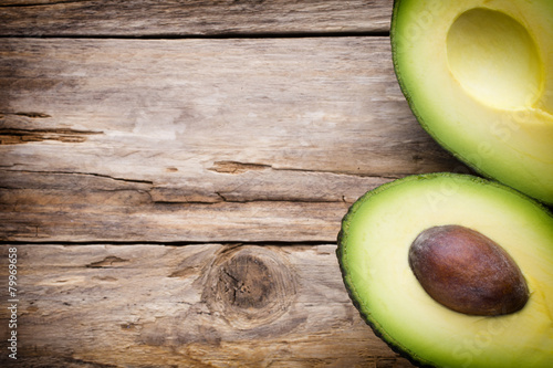 Fotografie, Obraz  Avocado parts on the wooden table.