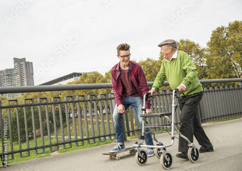 Glücklicher älterer Mann mit Rollator und erwachsener Enkel mit Skateboard