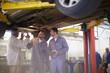 Zwei Kfz-Mechaniker mit Kunden in Reparaturwerkstatt