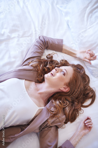 Happy woman lying on hotel bed