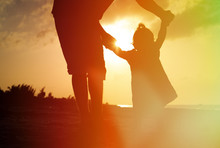 Silhouette Of Father And Little Daughter On The Beach