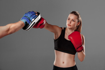 Fototapeta Sport beautiful woman is boxing on gray background