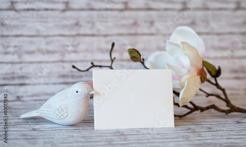 Fényképezés  Bird Figurine and Blank Card with White Blossoms