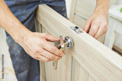 Obraz carpenter at door lock installation - fototapety do salonu
