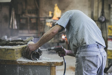 Man Working With Pneumatic Drill On Sculpture In A Foundry