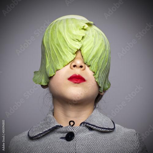 Fotografie, Obraz  Niña con hojas de repollo tapándole los ojos