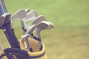 Fototapeta Golf set of golf clubs over green field background