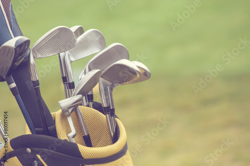 set of golf clubs over green field background - 80097454